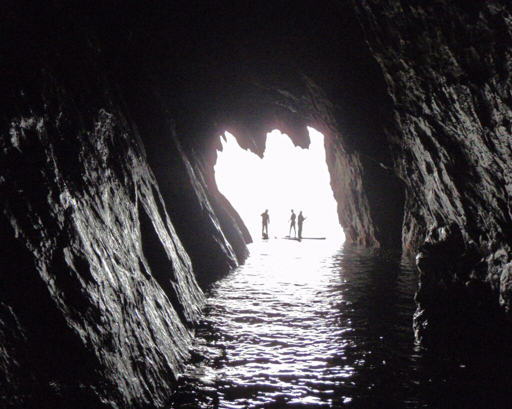 Stand Up Paddlers from a Sea Cave